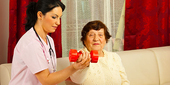 Female therapist helping elderly patient with barbell exercises