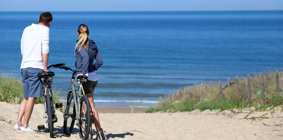 Couple with bicycles on beach in New Jersey