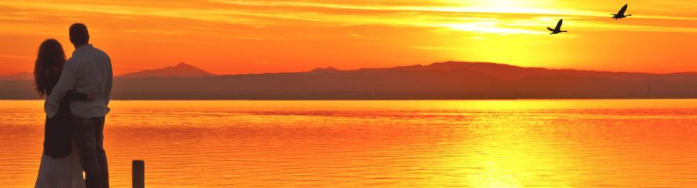 couple watching the sunset at a pier in north carolina - Nicu Travel Nursing